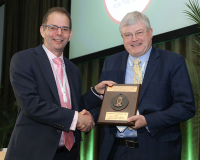 Andrew Lotery, MD, FRCOphth, (00F) presented the Singerman Medal to Stephen Russell, MD