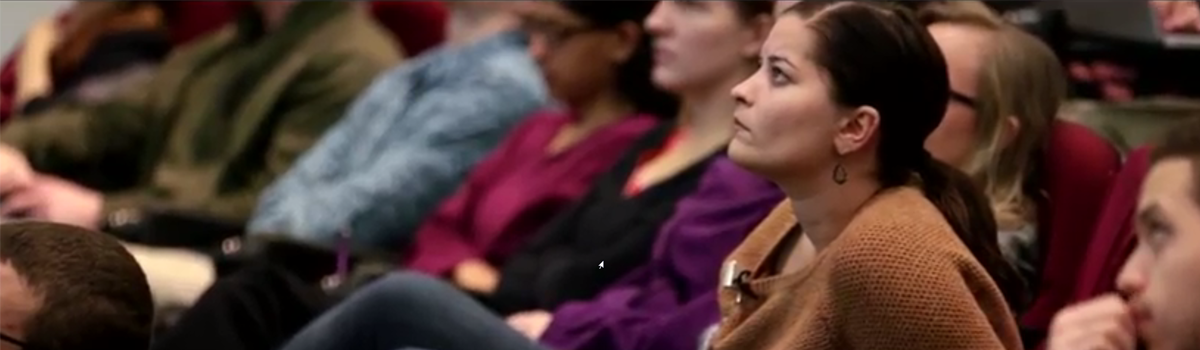 Students attending lecture, one of whom is in sharp focus