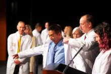 Associate Dean Chris Cooper helps a new student slip on his White Coat during the White Coat Ceremony