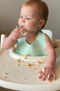 A baby eating in a high chair
