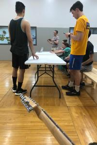 A point-of-view photo of students in a gym, sitting or standing around a folding table.  The photographer is holding a guitar.