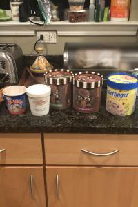 A photo of several containers of ice-cream sitting on a countertop