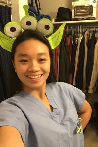 Photo of Melissa Chan in a bathroom wearing an alien on her head