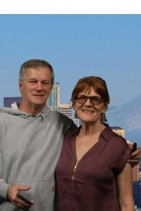 A composited photo of a couple standing in front of a backdrop of the Seattle skyline.