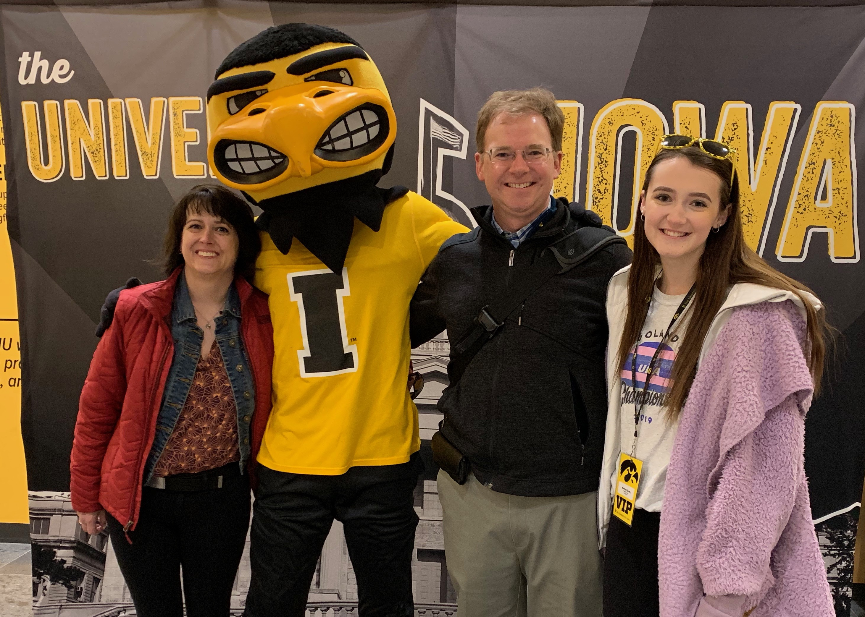 A family stands with their arms around a university athletics mascot