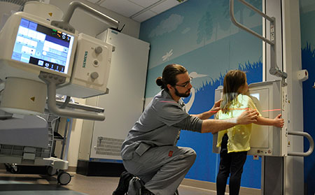 DMS tech positioning child for chest x-ray