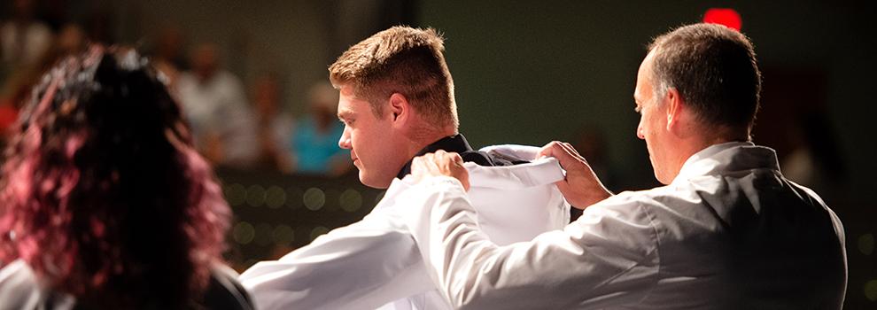 Student receiving white coat